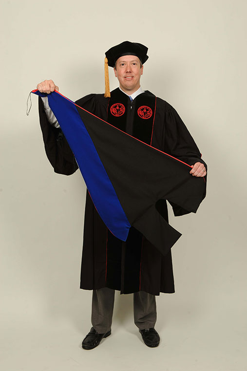 Student in commencement robe holds stole