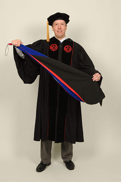 Student in commencement robe folds stole lengthwise