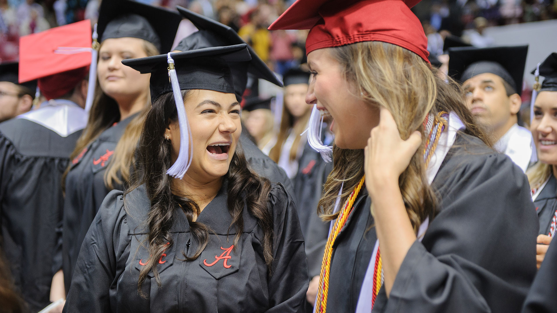 Two excited graduates having fun at commencement.