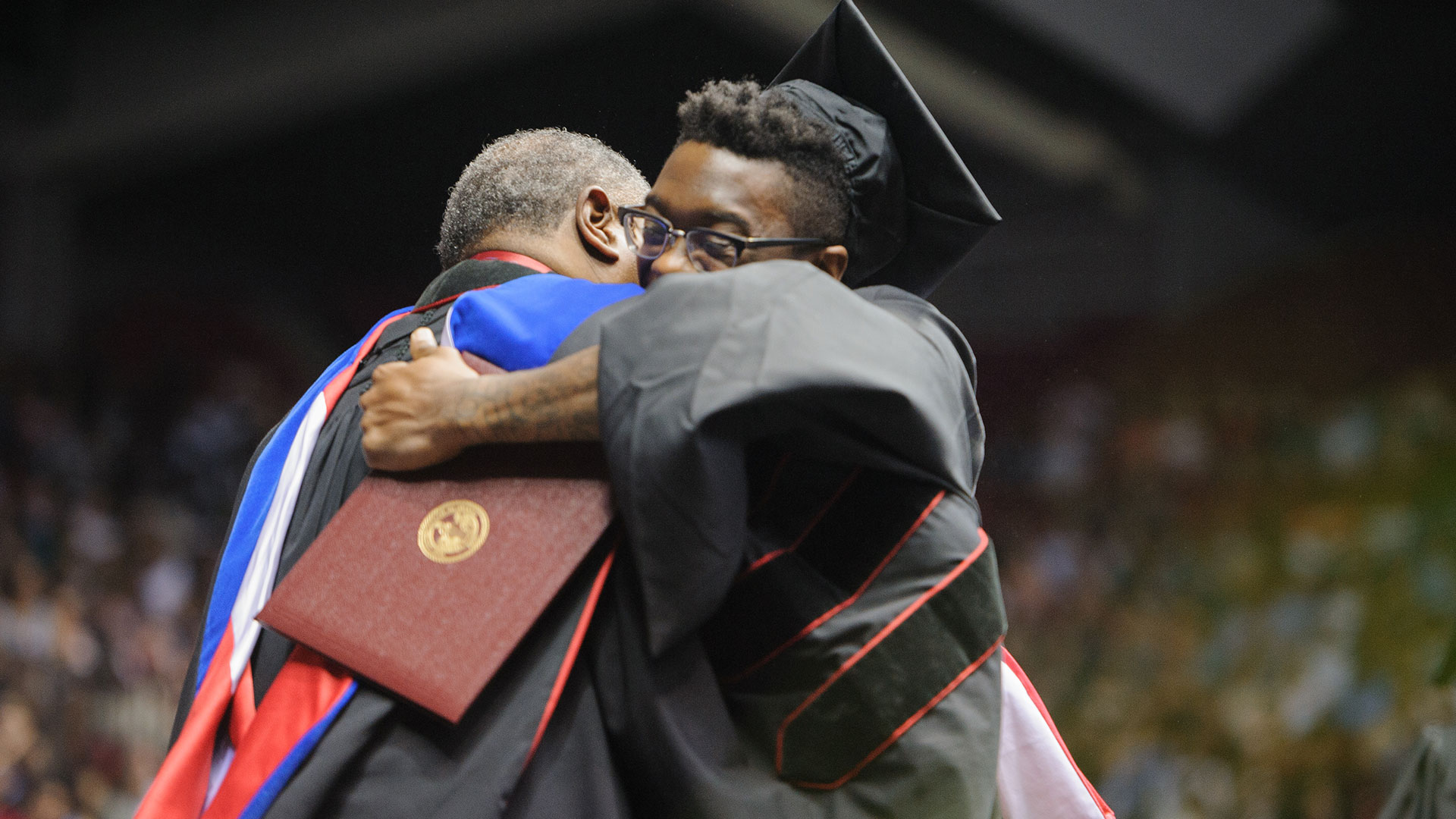 A graduate hugs a professor during his walk across the stage.