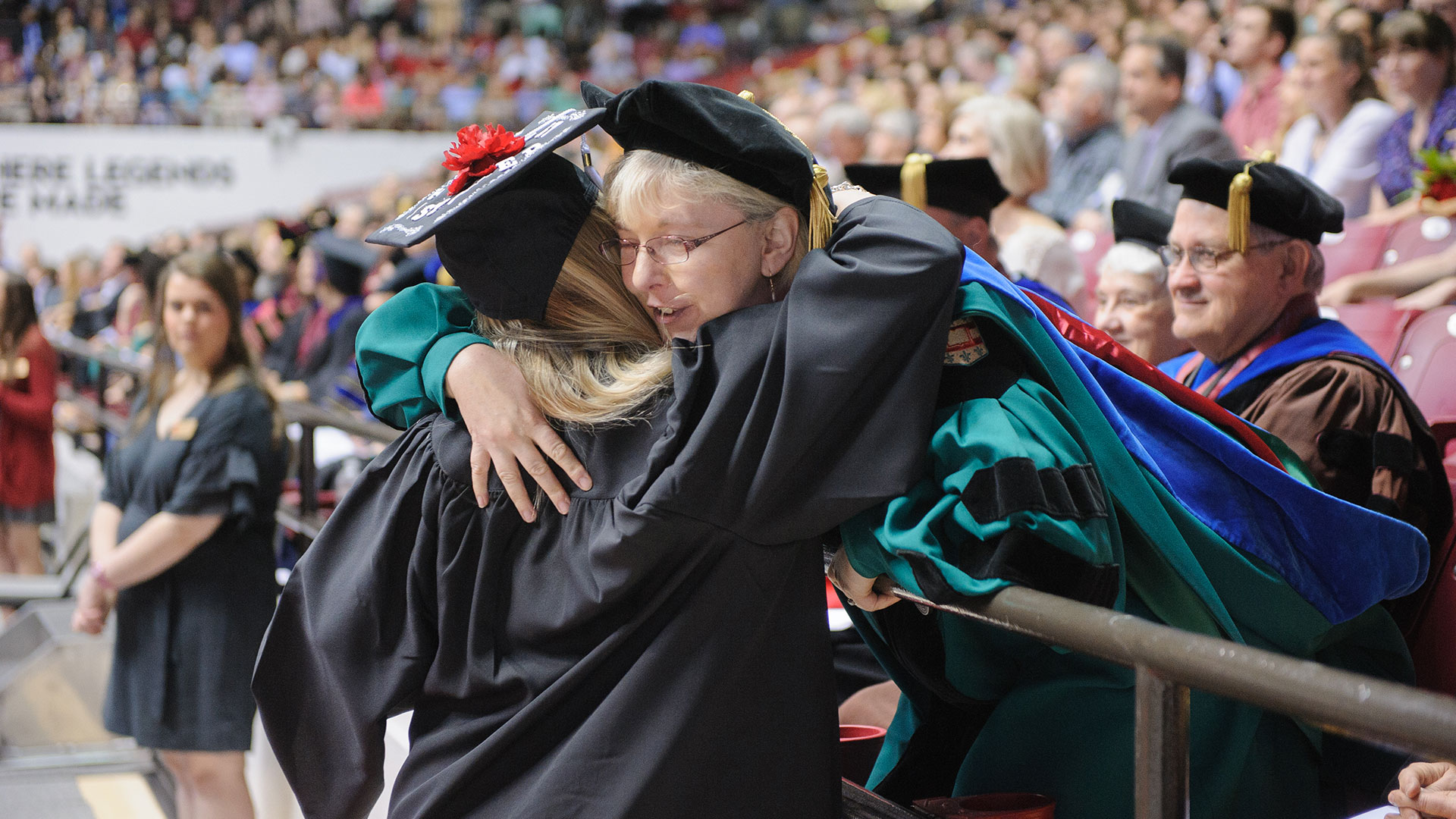 A graduate reaches up over the rails to hug a professor after her walk across the stage.