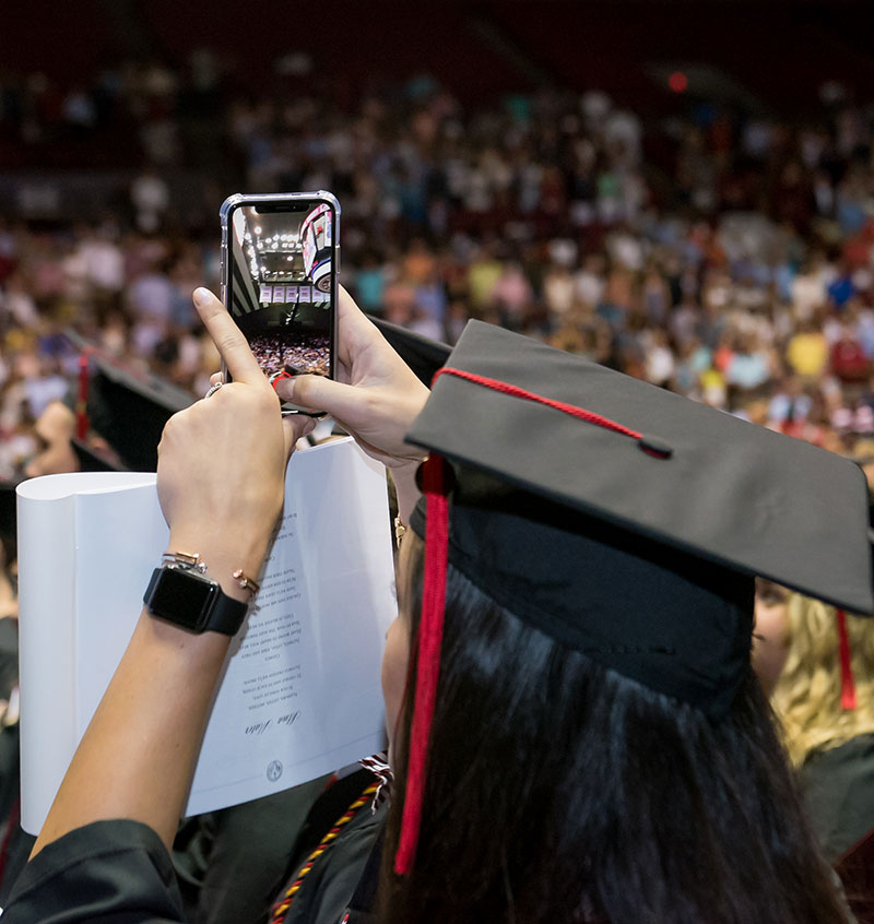 Grad with phone taking a picture.