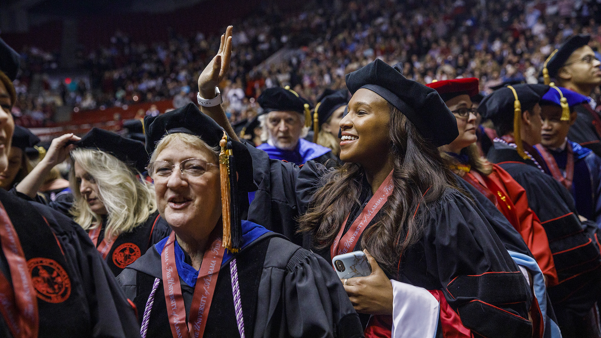 A doctoral graduate waves to family.
