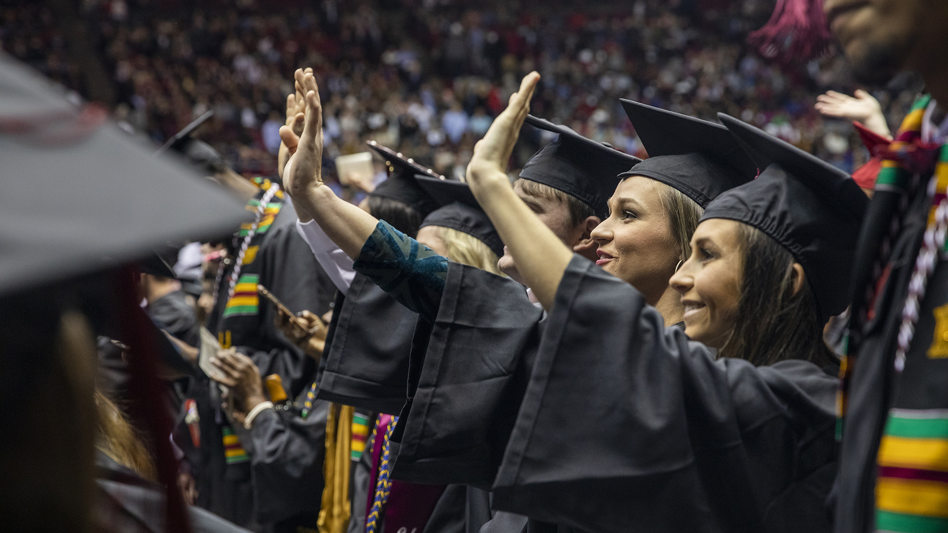 A row of graduates waving to friends and family.