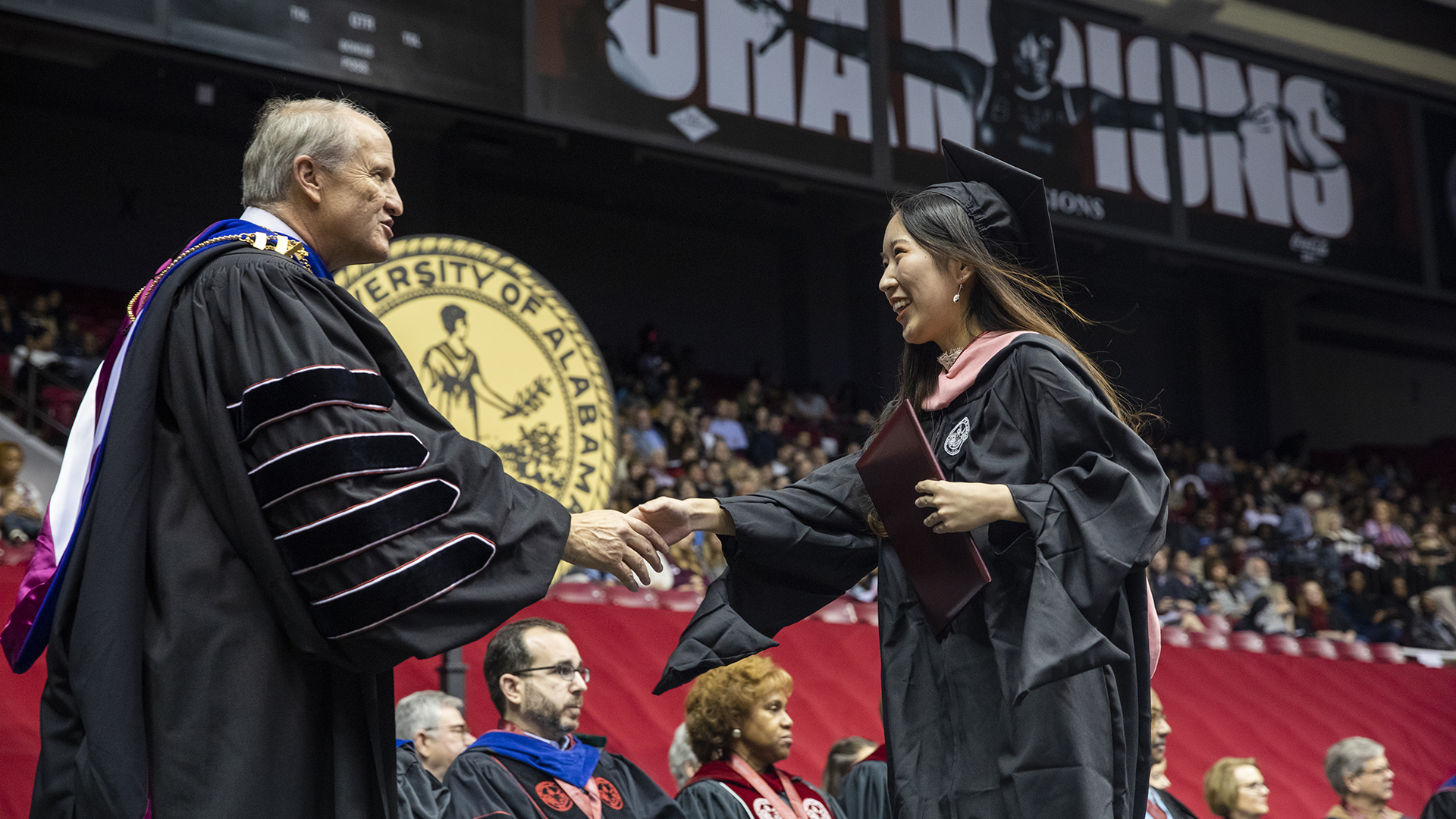 A graduate shakes Dr. Bell's hand.