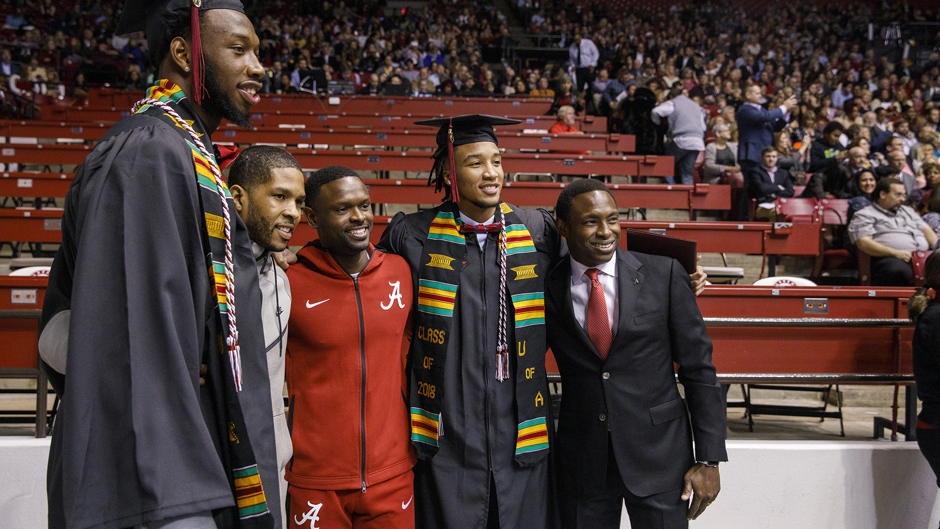 Two graduates pose for a picture with friends and a man in a suit.