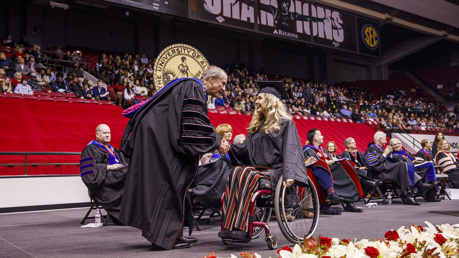 A graduate in a wheelchair shakes Dr. Bell's hand.