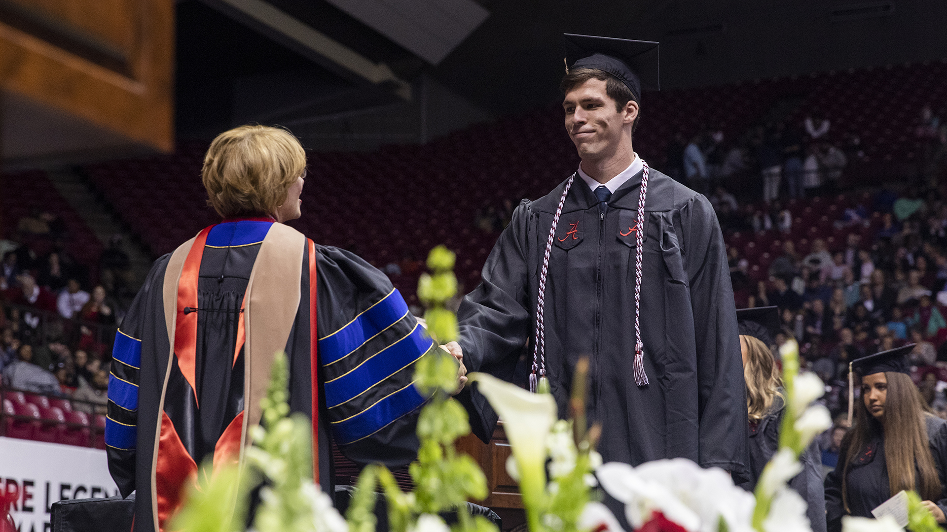 A graduate shakes a professor's hand as he crosses the stage.