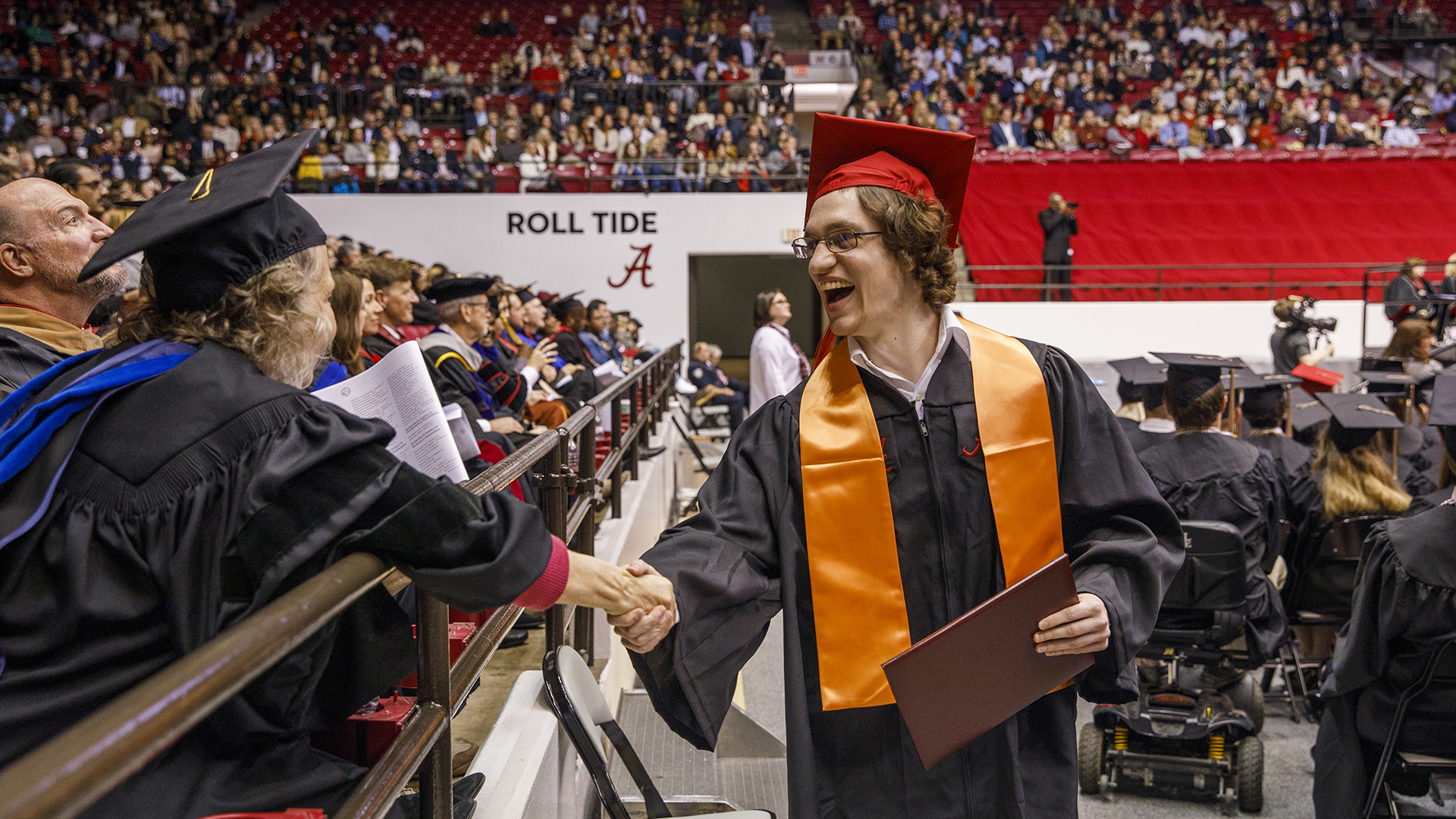 A graduate shakes hands with a professor as they walk past the stands.