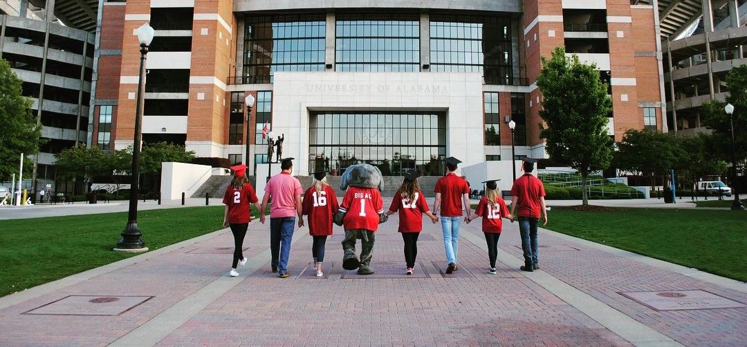 Group photo of 7 grads with Big Al walking towards Bryant-Denny Stadium