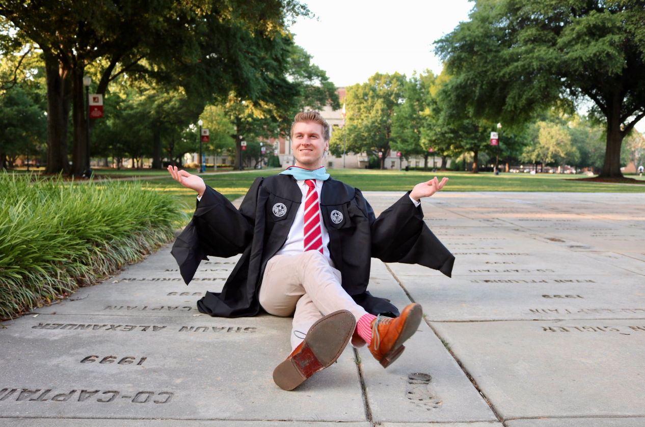A male grad sits at the base of denny chimes with Gorgas Library in the background.