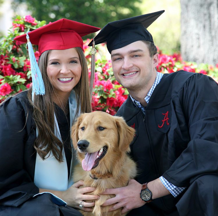 Two graduates pose with a dog outside