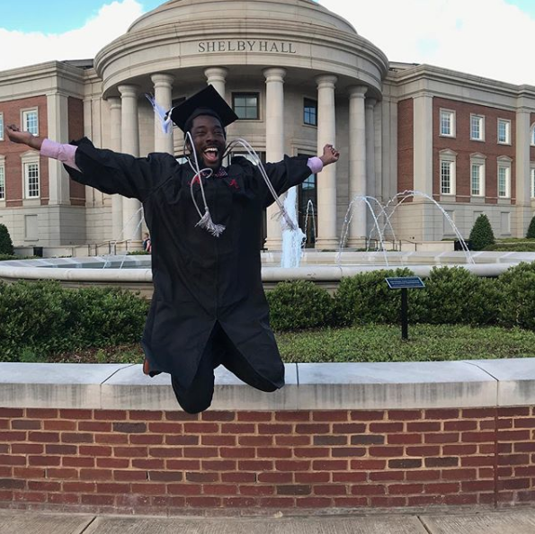 A male graduate jumps enthusiastically outside of Shelby Hall.