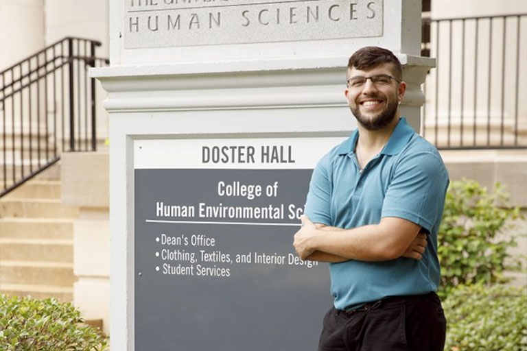 Tyler Higginbotham stands next to the Doster Hall building sign.