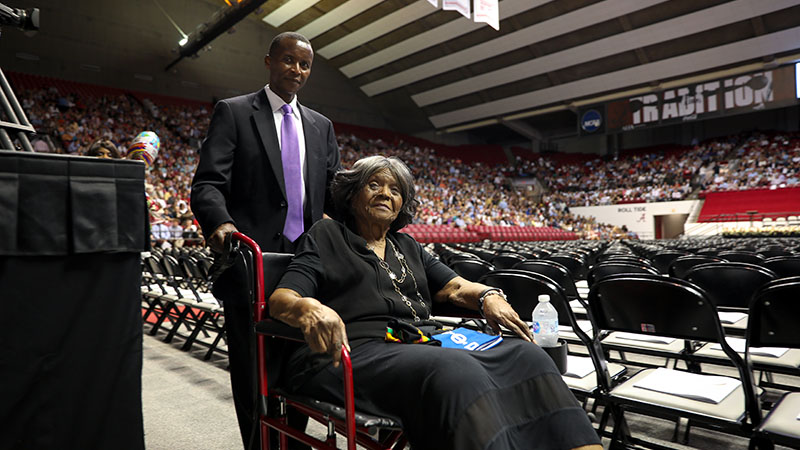 Autherine Lucy Foster in wheelchair being pushed towards the commencement ready room.