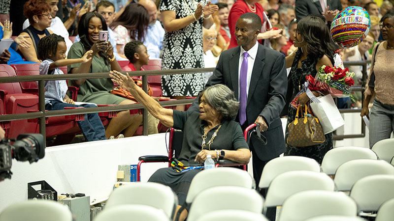 Autherine Lucy Foster waving to her family in the stands as she passes.